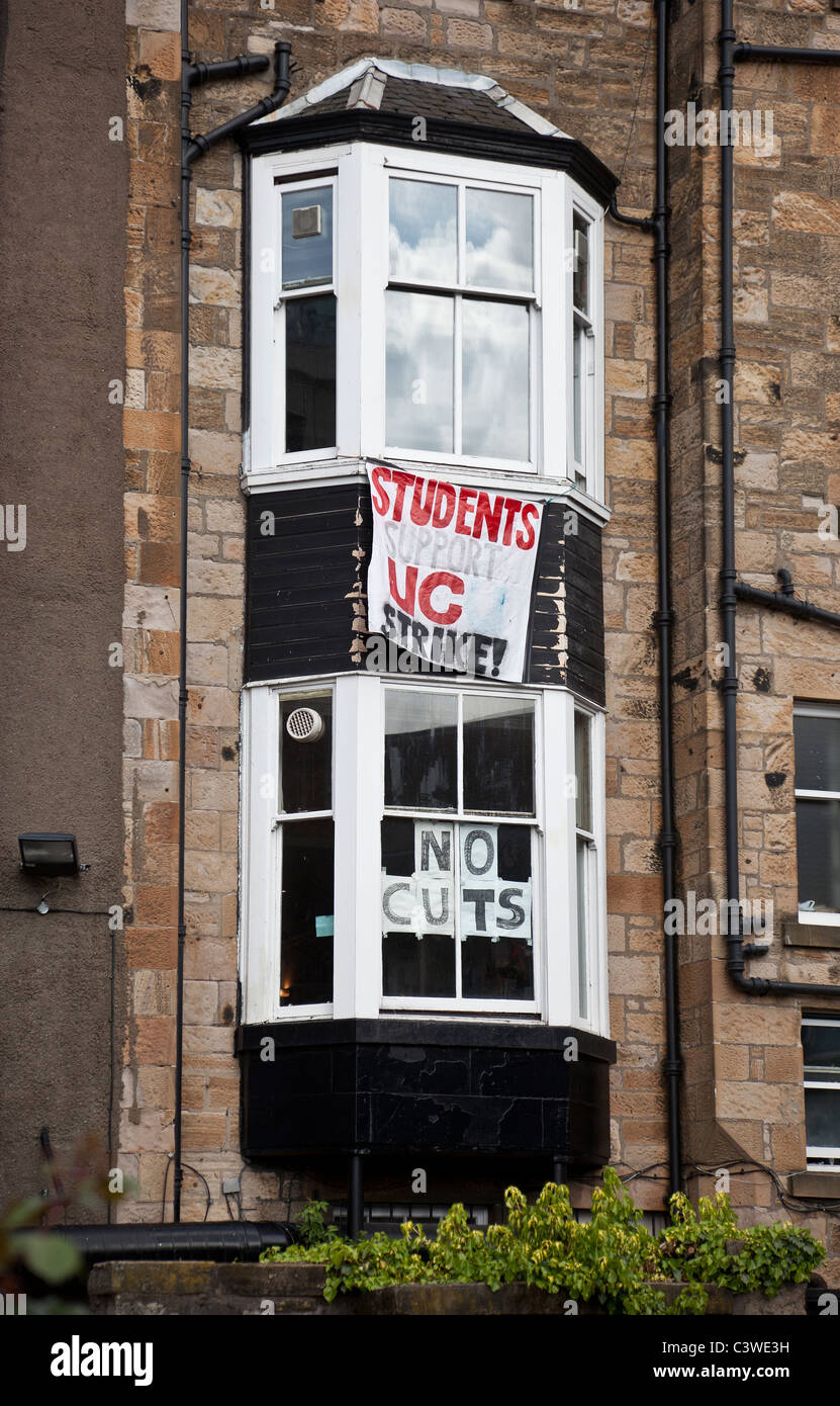 Window with sign and banner protesting against the budget cuts at Glasgow University, Scotland, UK - Stock Image
