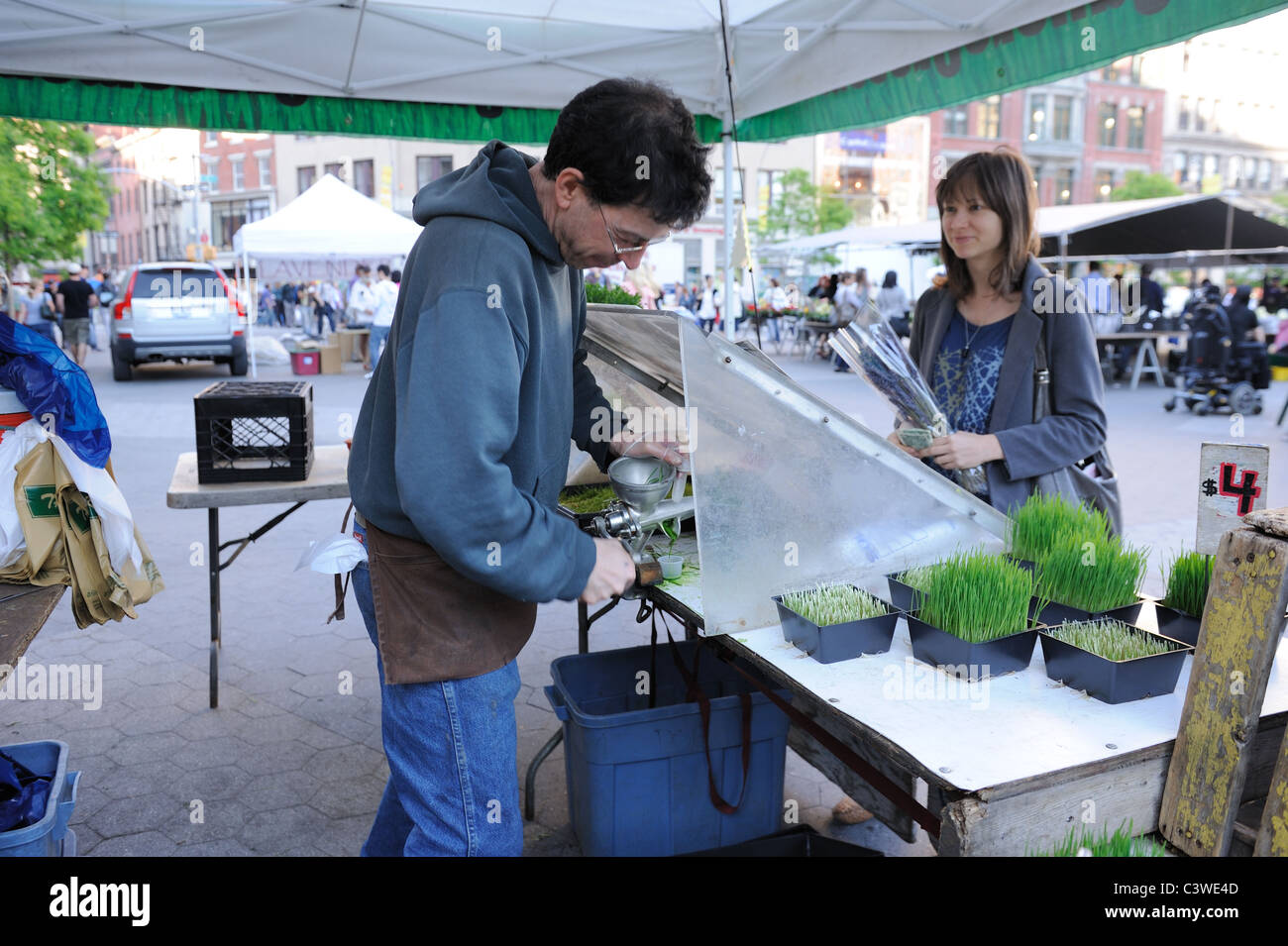 A farmer juicing wheatgrass for a customer in the Union Square farmers' market. - Stock Image