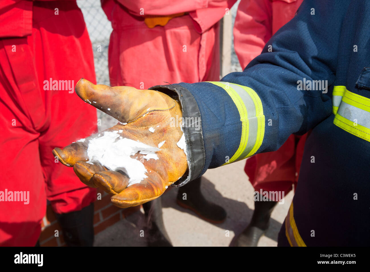 A fireman demostrates the frozen residue from a C02 fire extinguisher. - Stock Image