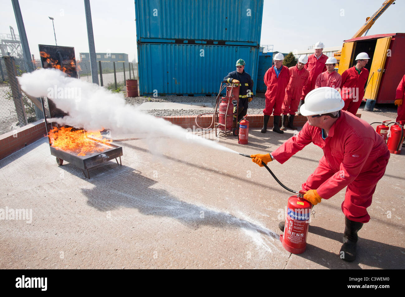 Workers in the offshore industry practice fire fighting with a powder extinguisher as part of an industry training - Stock Image