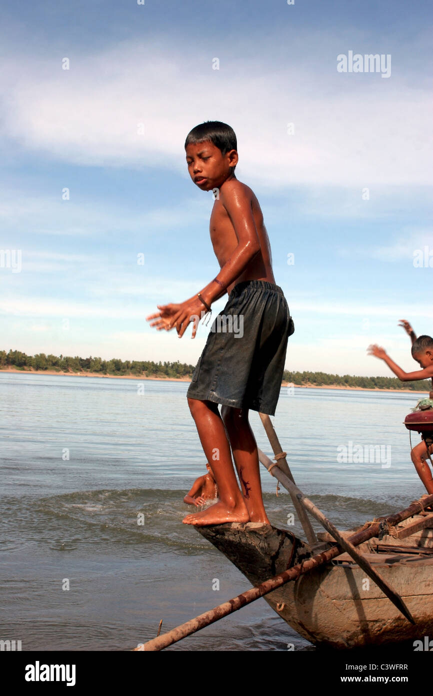 Three young Asian boys are using an old wooden fishing boat as a diving  platform on the Mekong River in Kratie, Cambodia.