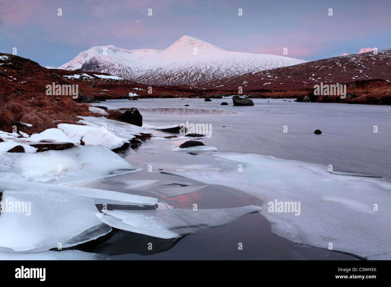 Snow-clad Meall a Bhuiridh and the icy waters of Lochan na h-Achlaise in Rannoch Moor, Scotland - Stock Image