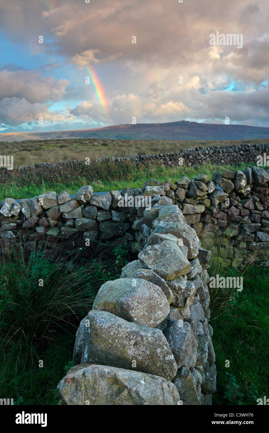 A rainbow forms over Simon's Seat near Howgill in the Yorkshire Dales of England - Stock Image