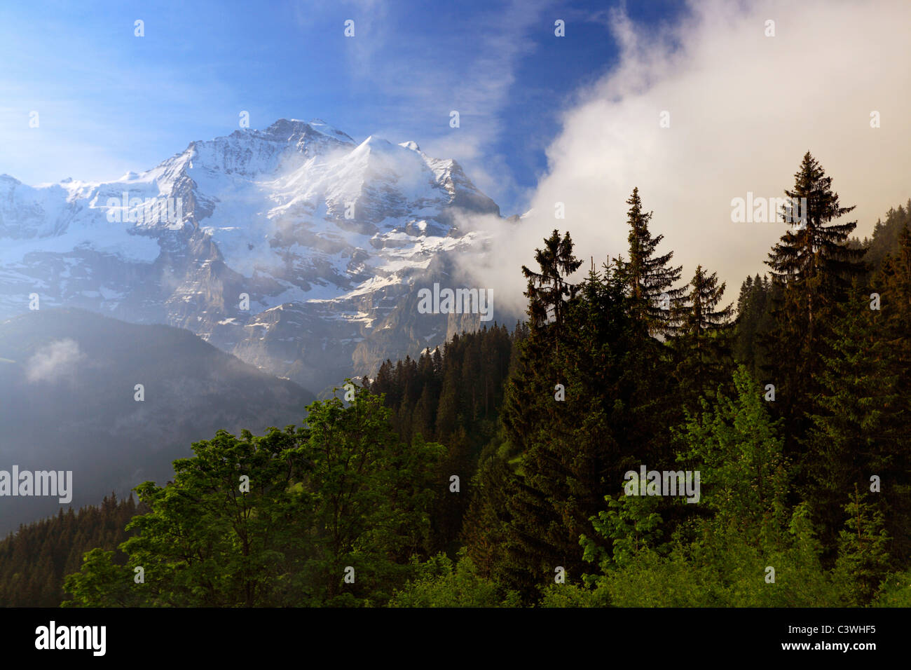 Morning fogs lifts to reveal the alps near Murren in Switzerland - Stock Image