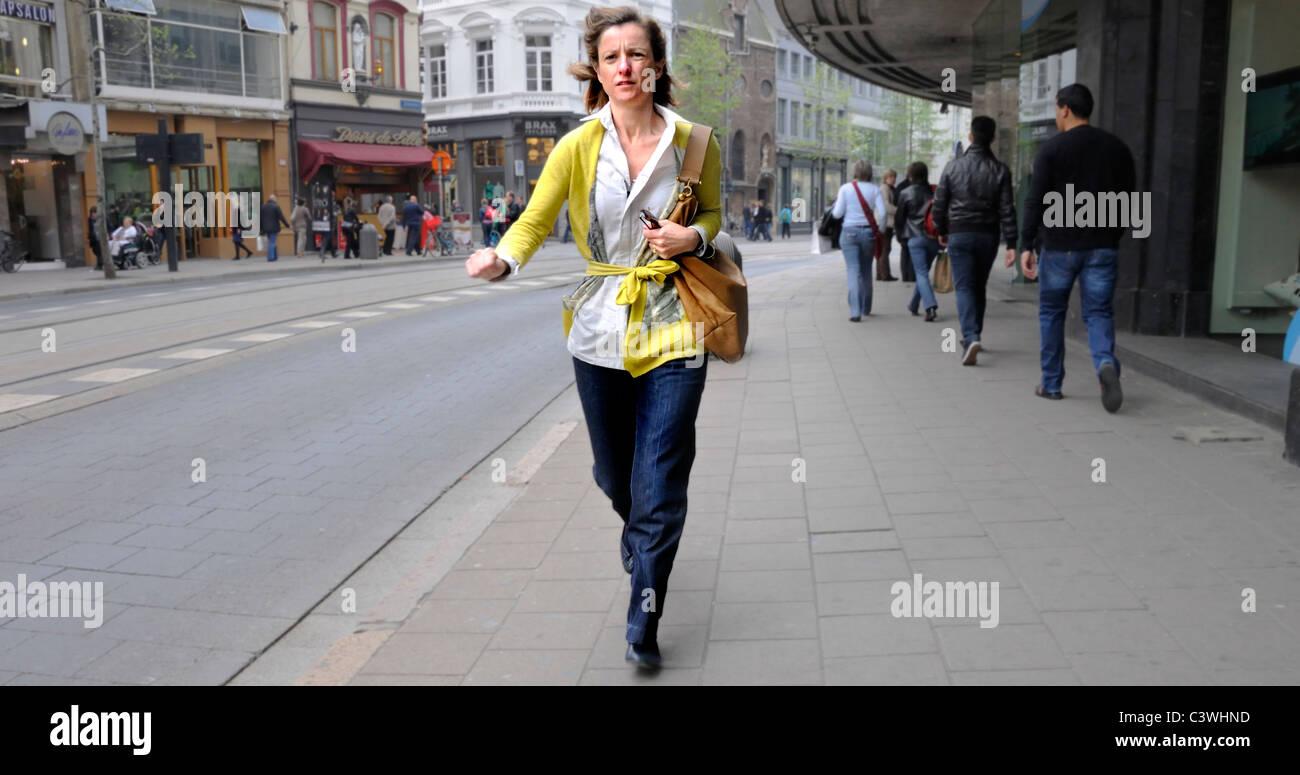 Antwerp / Antwerpen, Belgium. Woman walking quickly through city centre - Stock Image
