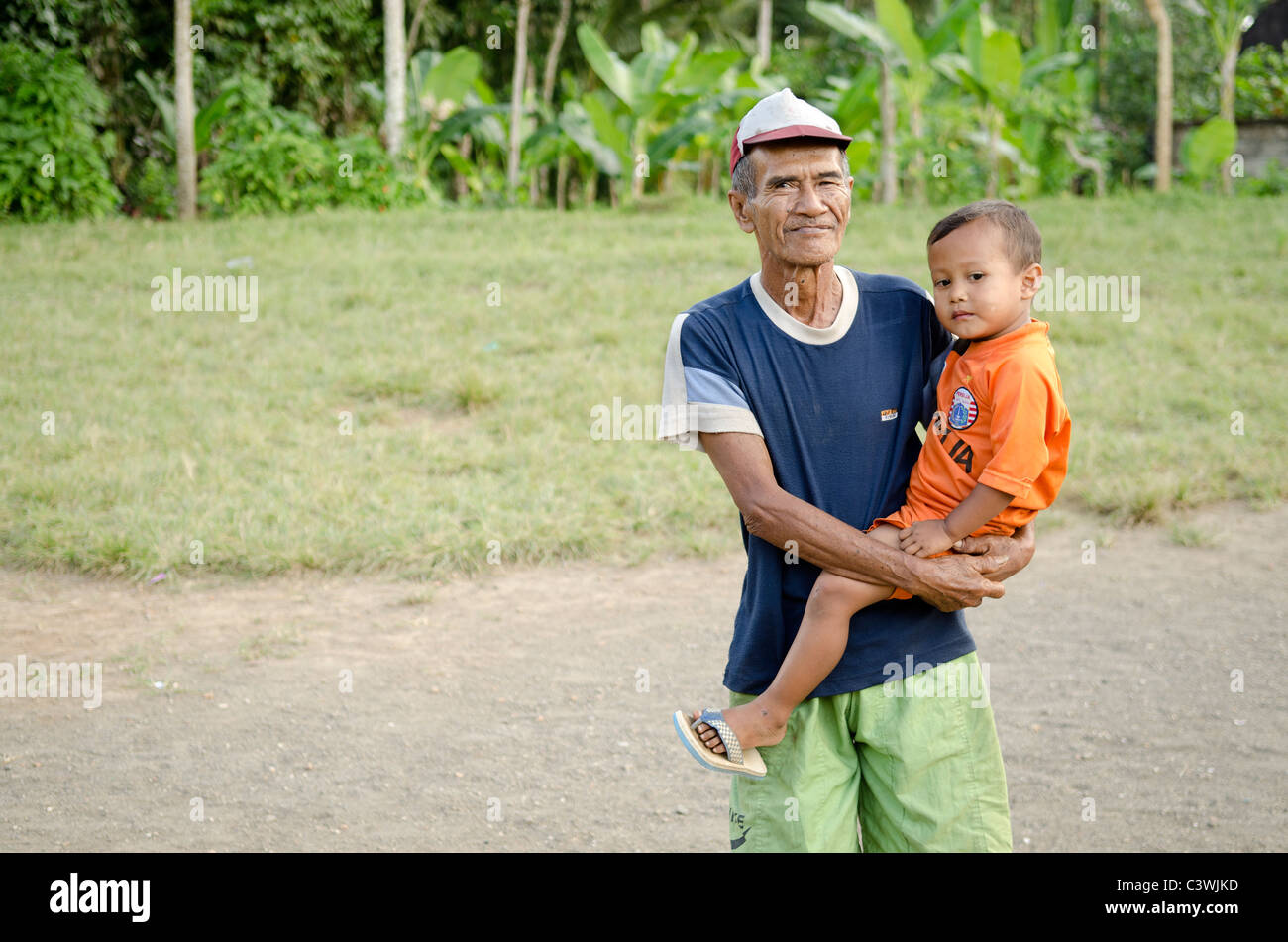Old Man With Child In Bali Indonesia Village Stock Photo