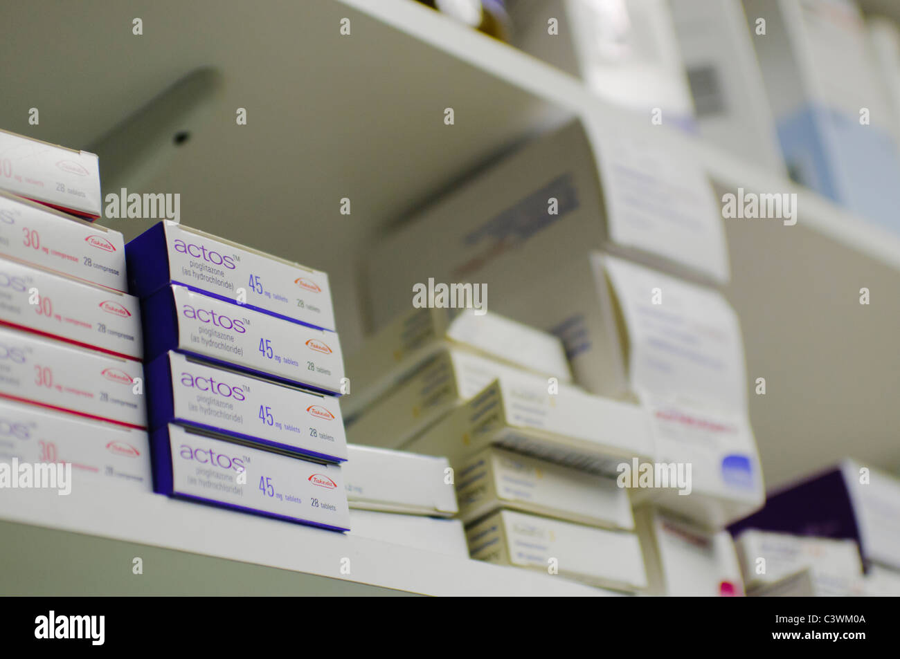 Boxes of prescription tablets on a pharmacy shelf - Stock Image