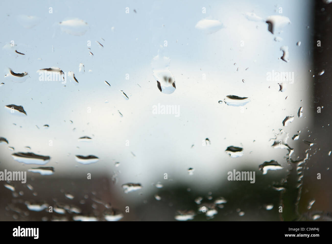 Rain drops on the window and blurred sky and house in the background - Stock Image