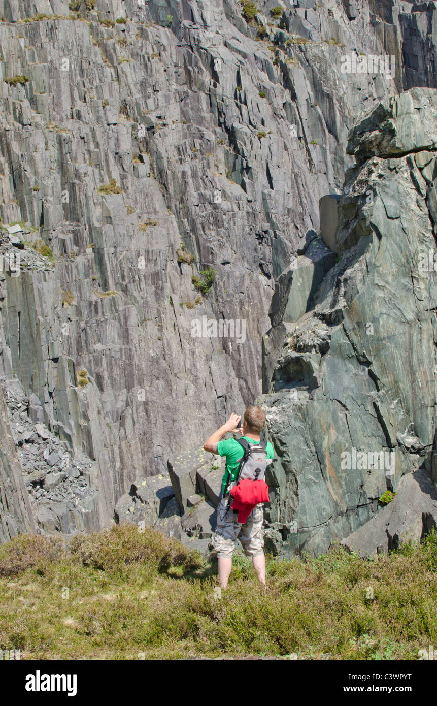 Young man taking a photo with a mobile phone of the main groove on The Quarryman, Dinorwig slate mine, Snowdonia, - Stock Image