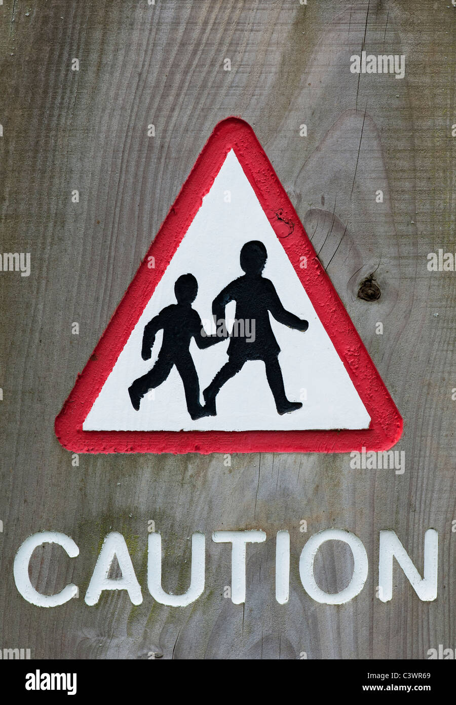 Triangular Pedestrian crossing caution sign carved into wood - Stock Image
