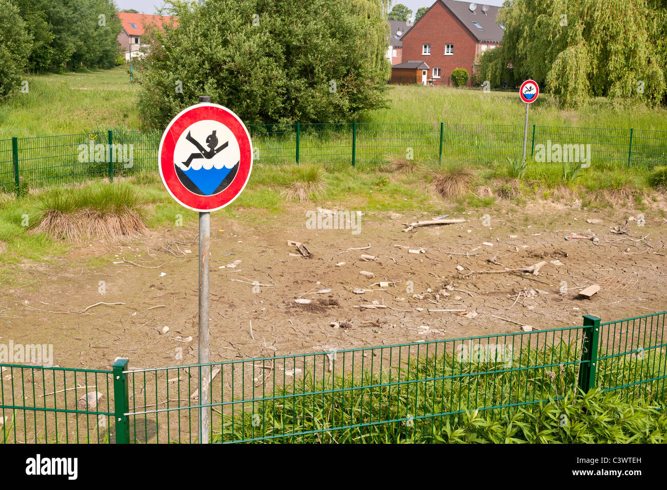 A pond is completely dry after several weeks of drought. - Stock Image
