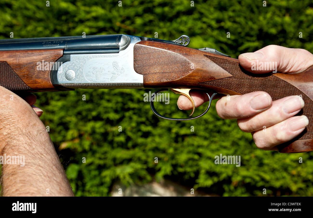 man holding shotgun with finger on the trigger.landscape format.copy space. - Stock Image