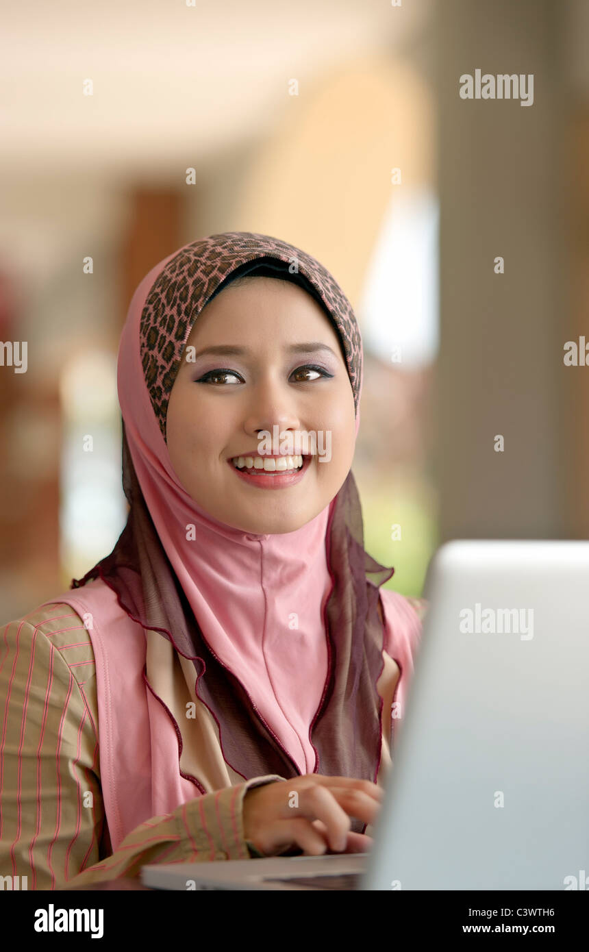 Young pretty Asian muslim woman smiles while typing notes on laptop in cafe - Stock Image