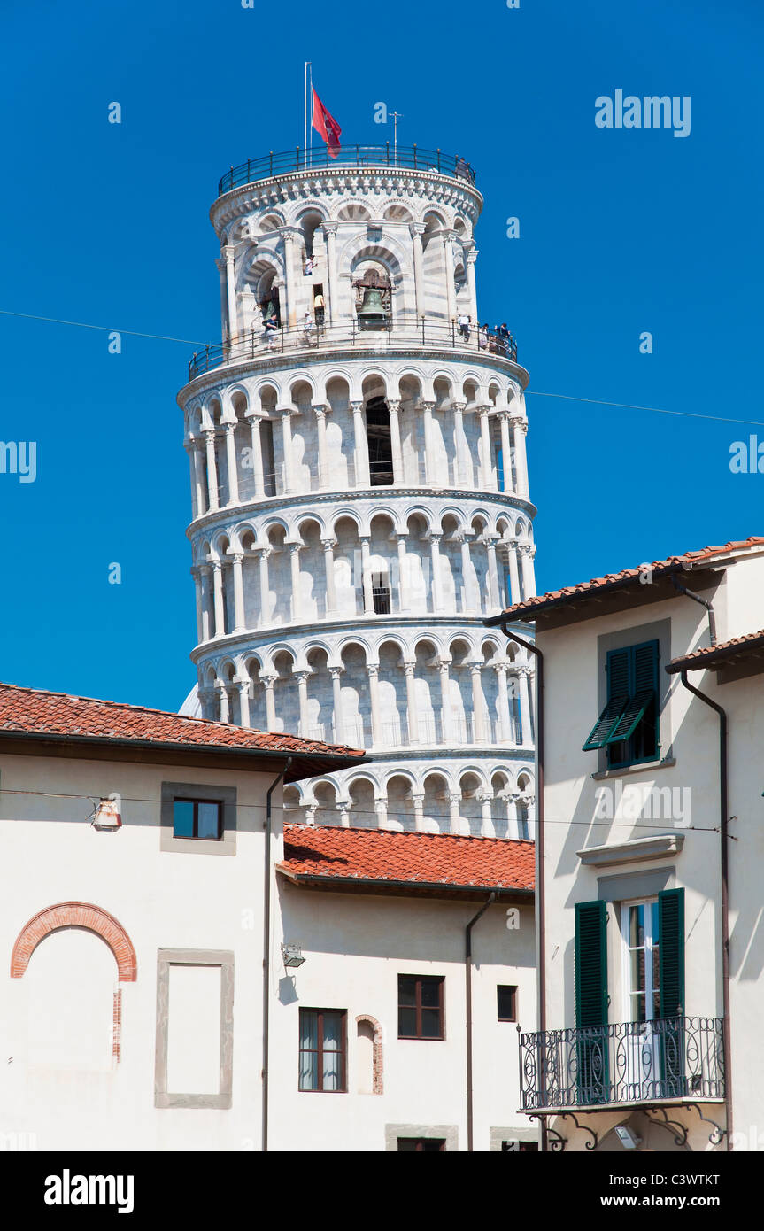 The famous Leaning Tower standing out against the sky behind the buildings of the city centre, Pisa, Tuscany, Italy Stock Photo