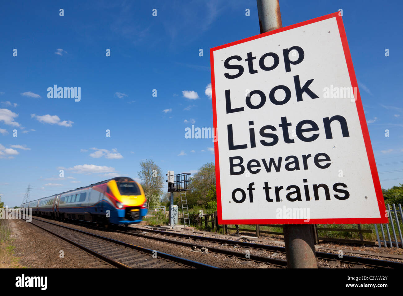 Speeding train passing a railway crossing sign England GB UK - Stock Image