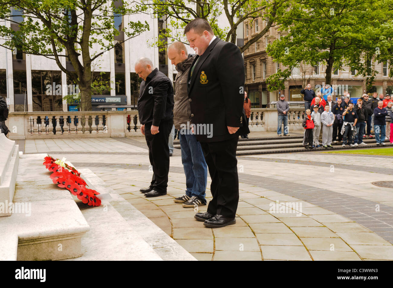Three men lay poppy wreaths at a wreathlaying ceremony Stock Photo