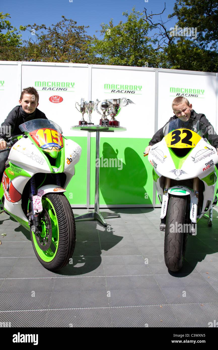 Two young motorbike enthusiasts posing on race trim bikes England UK - Stock Image