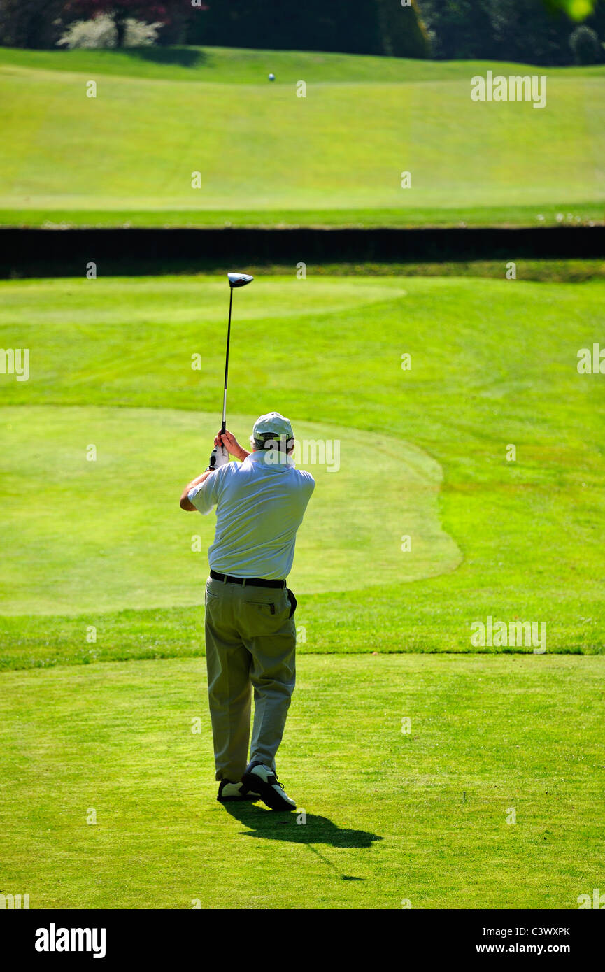 A golfer driving off down the fairway, over a stream, with the ball visible in the distance - Stock Image