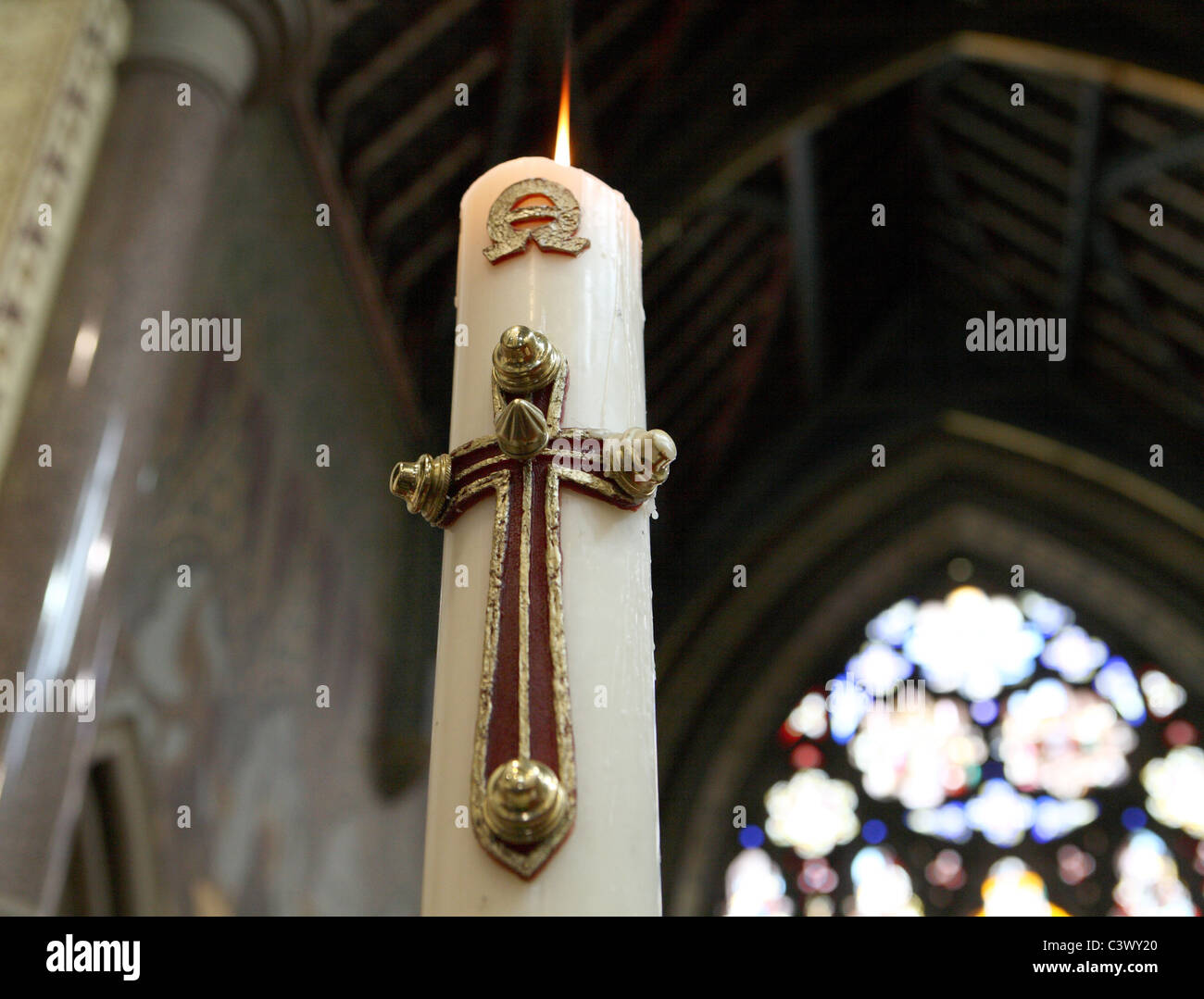 Mass Beeswax candle lit at a holy communion service - Stock Image