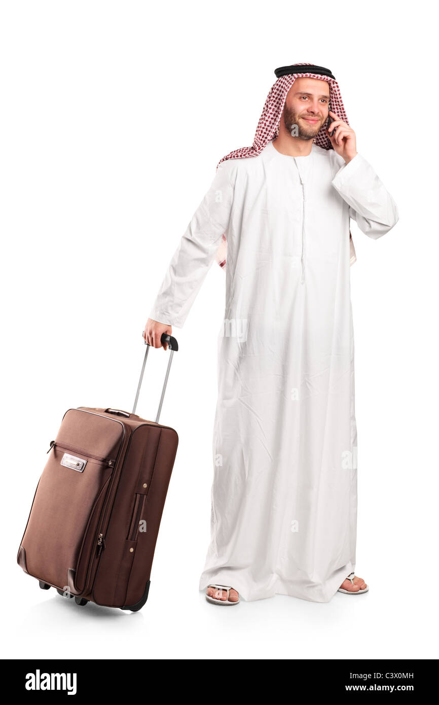 Arab tourist carrying a suitcase and talking on a mobile phone isolated on white - Stock Image