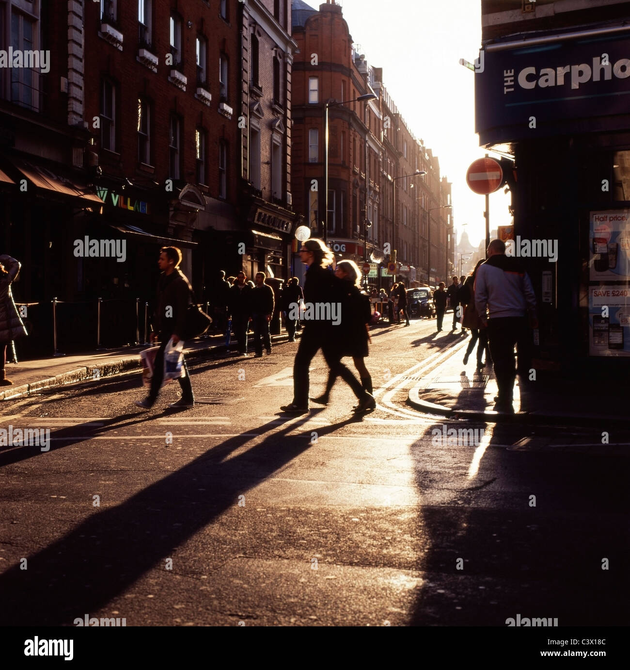 People on late Saturday afternoon in winter on the corner of Brewer and Wardour streets Soho London England  KATHY Stock Photo