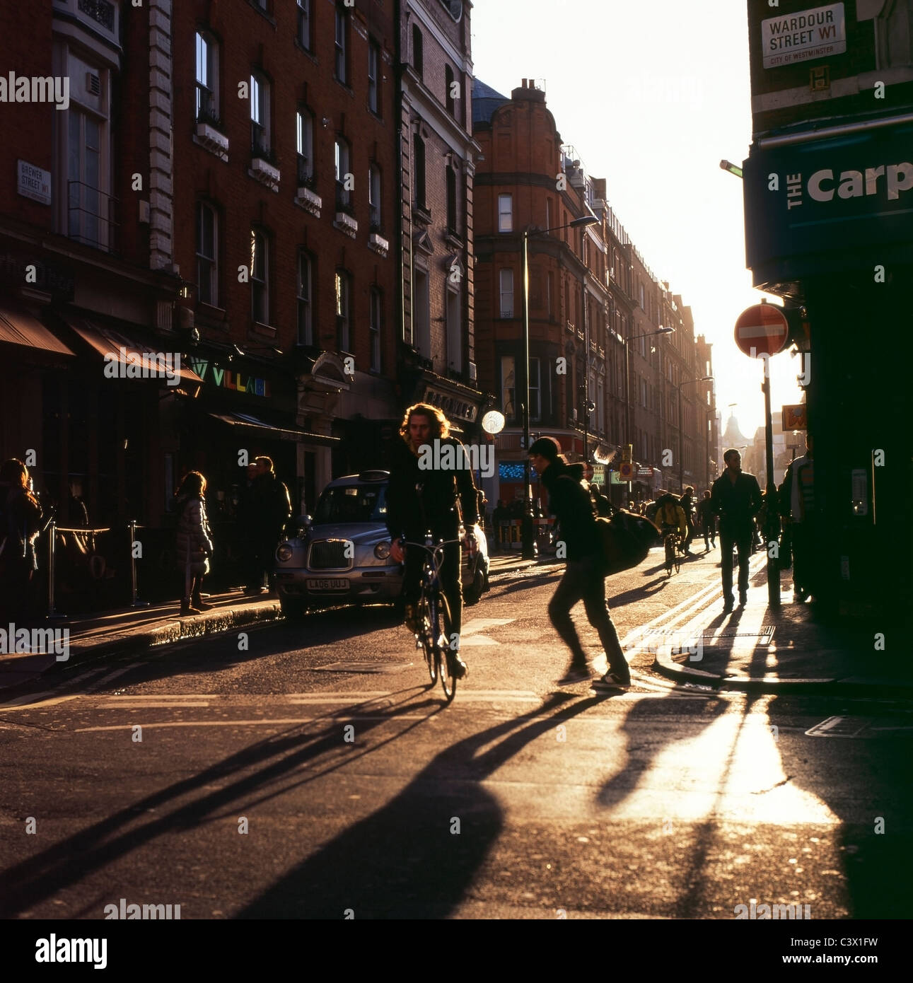 Cyclist and pedestrian cross road at corner of Brewer and Wardour street in late afternoon sunshine on in Soho London - Stock Image