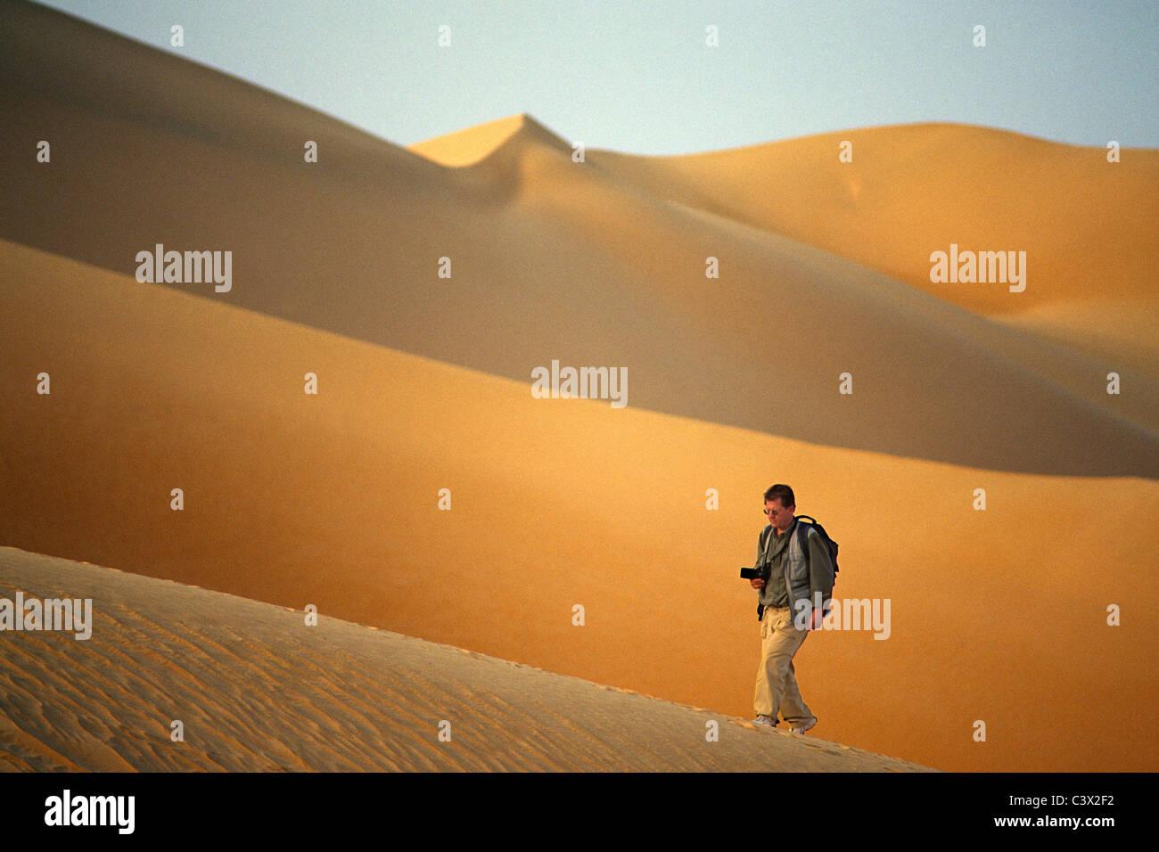 Algeria, Djanet, Sahara Desert, Photographer Frans Lemmens walking on sand dune. - Stock Image