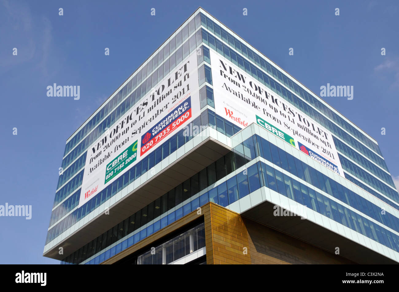 Large advertising panels on corner of modern office building to let at Westfield shopping centre beside Stratford - Stock Image