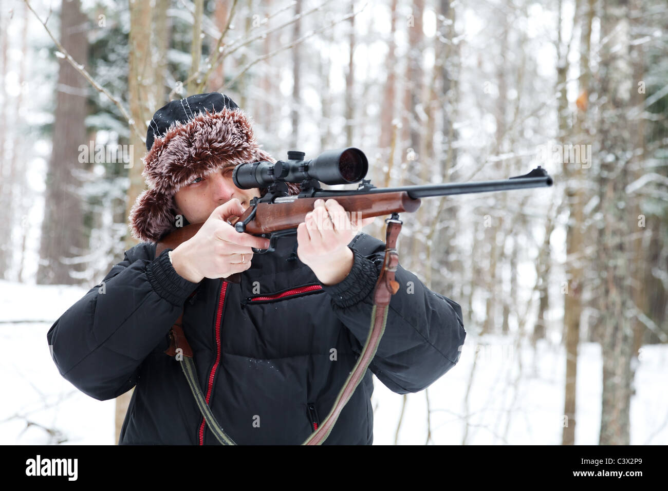 65fe5896b0e Hunter in a fur cap with ear flaps with sniper rifle in winter forest. -