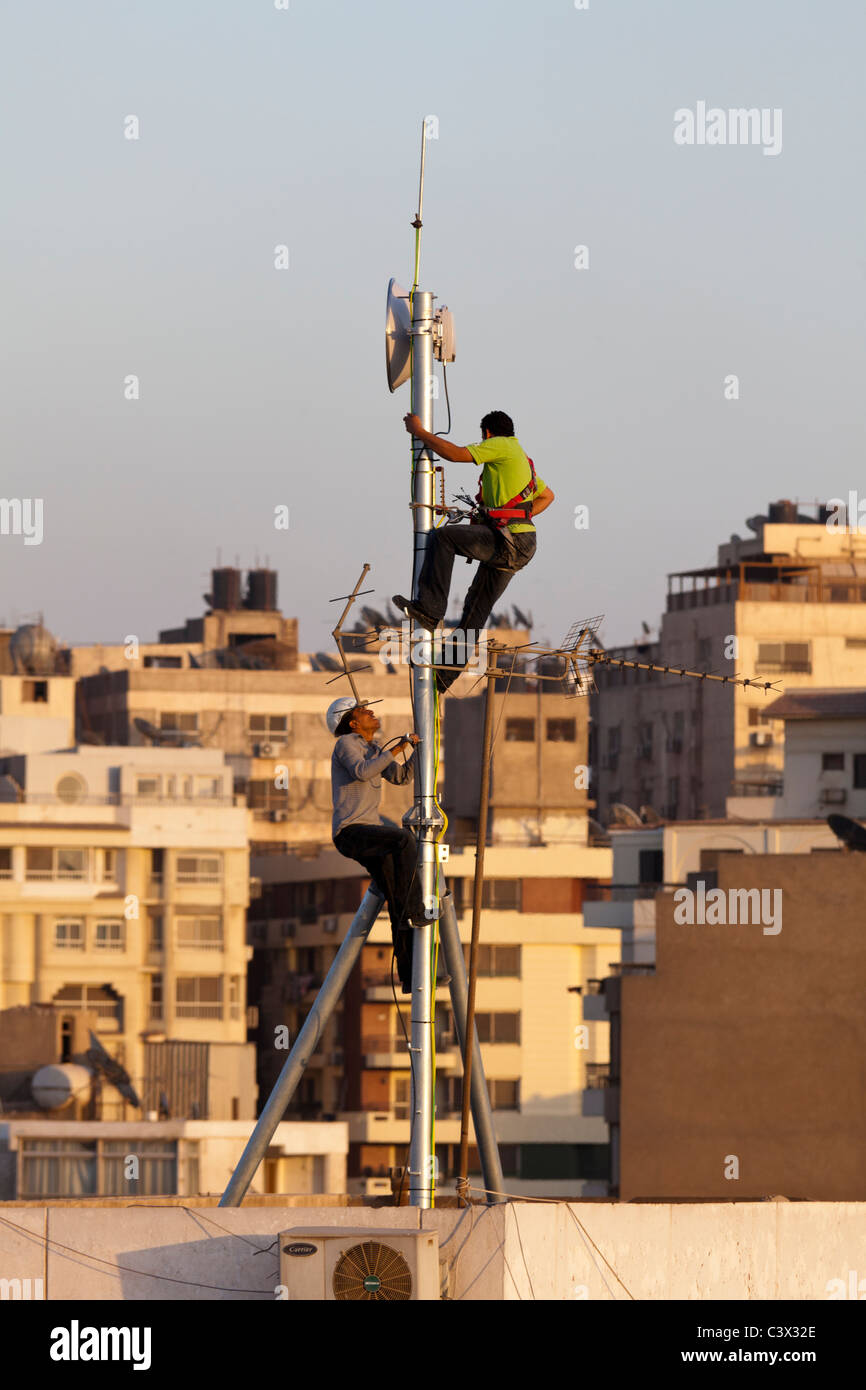 two workmen fixing aerial antenna on roof of building, Maadi, Cairo, Egypt - Stock Image