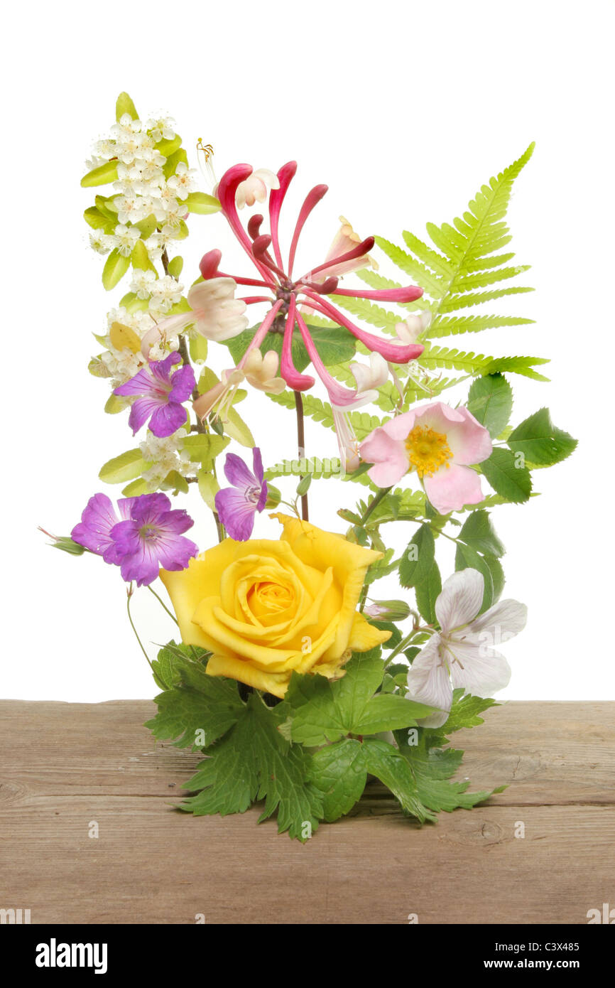 Mixed flower arrangement on an old wooden board against a white background - Stock Image