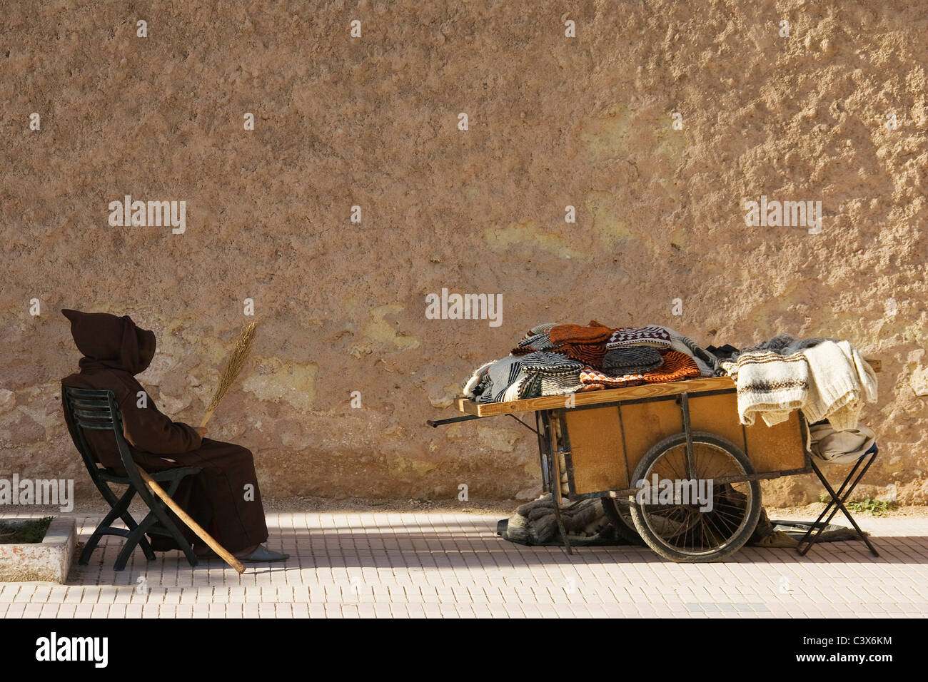 Old man and his handcart with woollens for sale at the city wall of Essaouira, Morocco - Stock Image