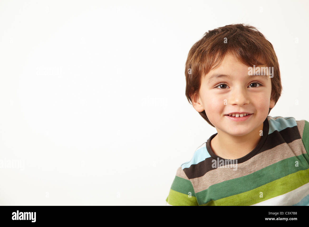 Young boy smiling on white background - Stock Image