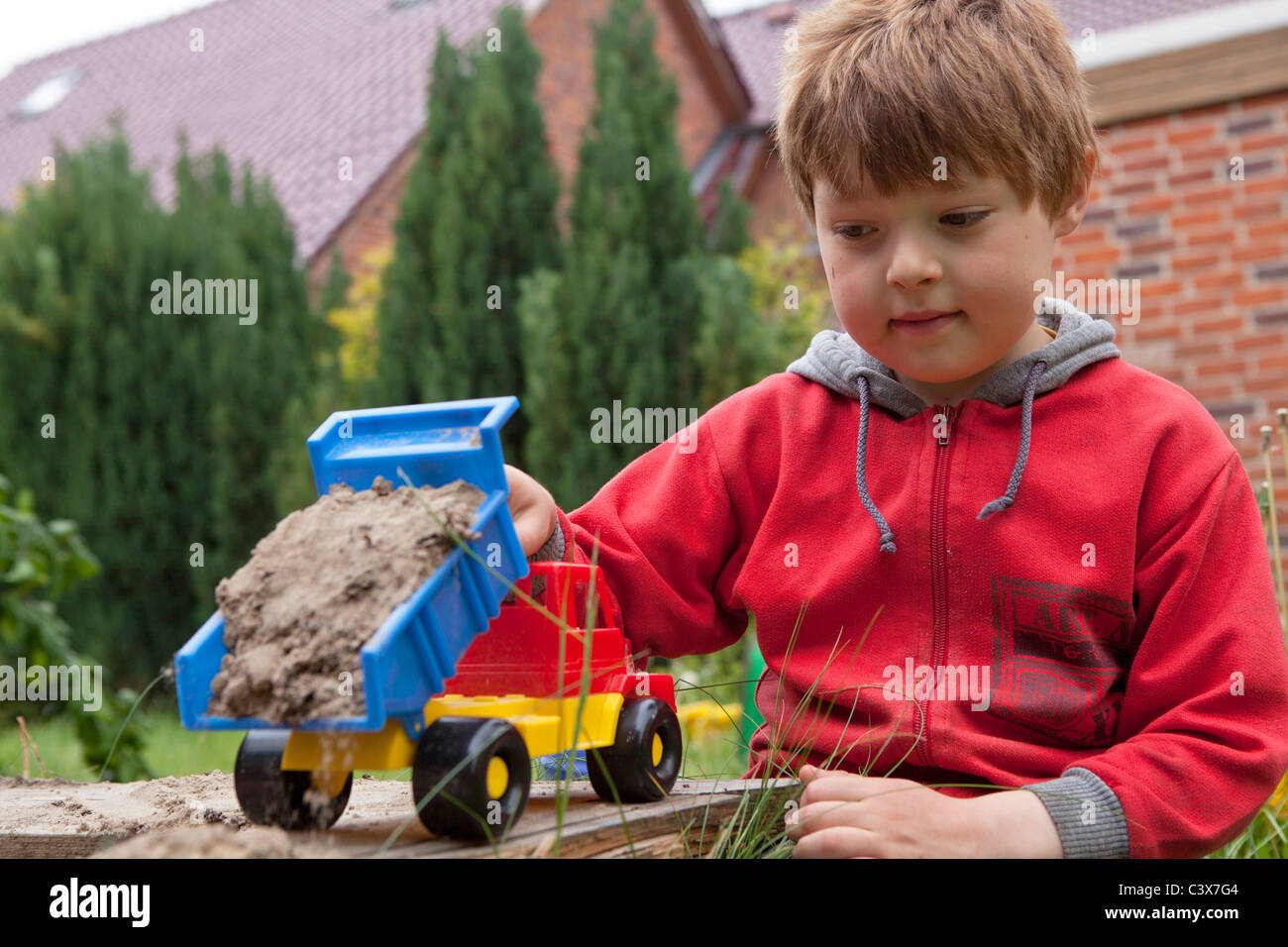little boy playing with a toy truck in a sandbox - Stock Image