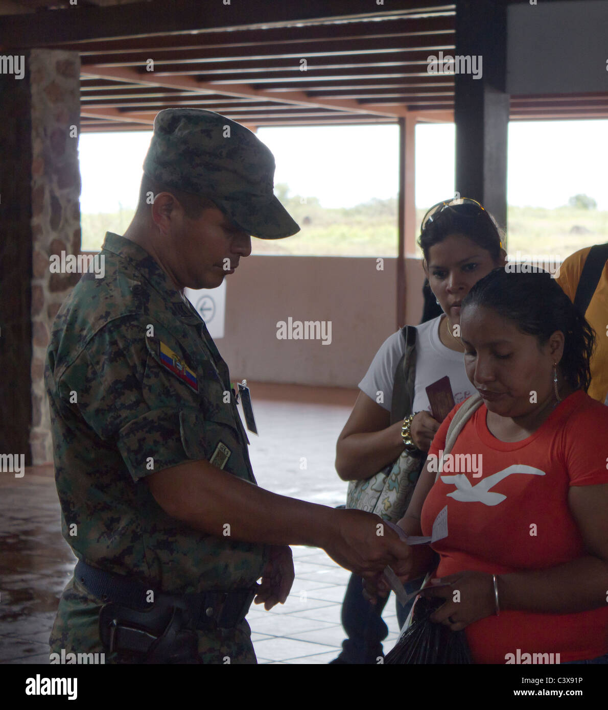army official checking passport of traveller, Seymour airport, Baltra Island, Galapagos Islands, Ecuador - Stock Image