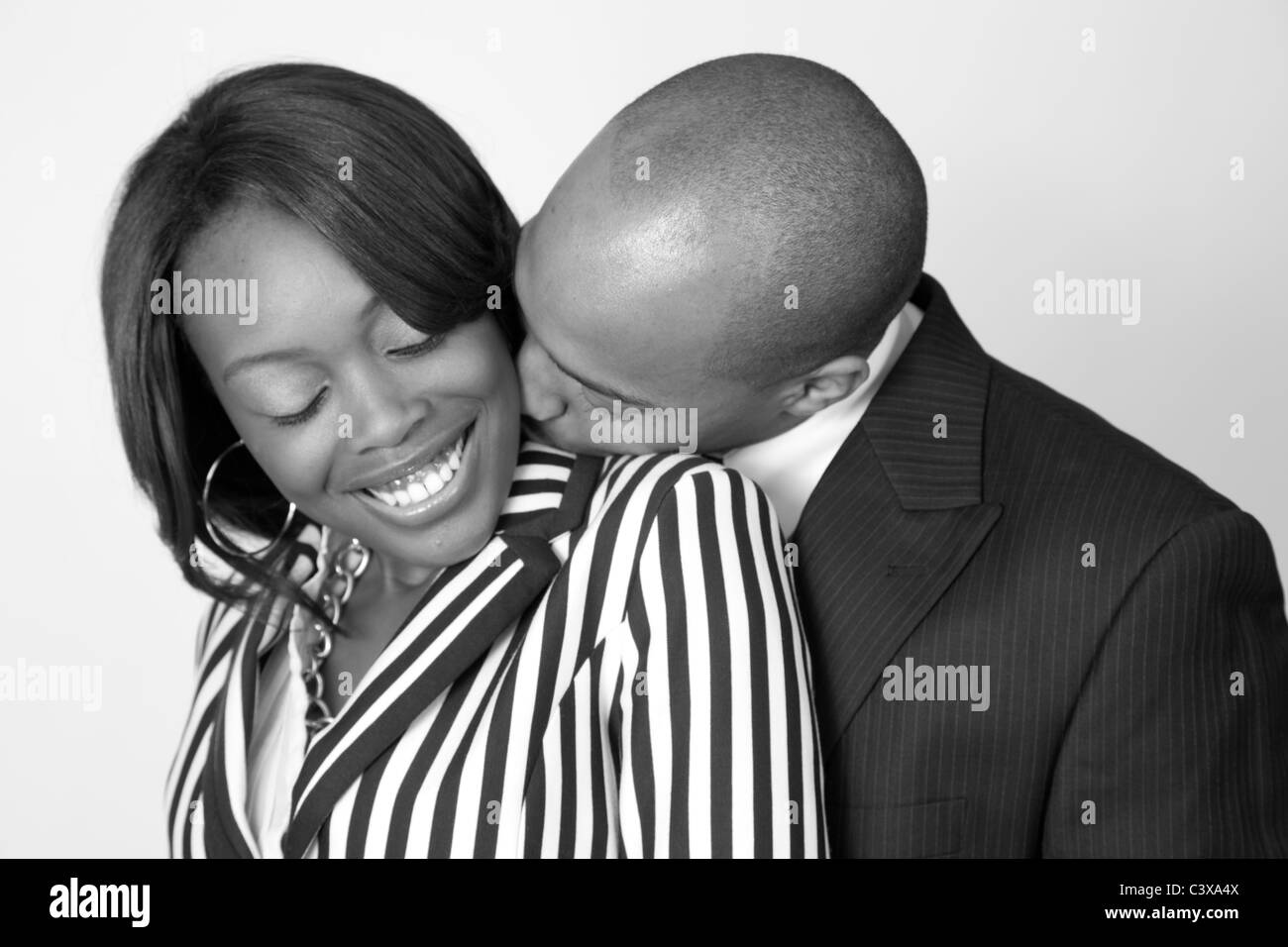 Cute romantic black couple standing together with affection and joy and a kiss