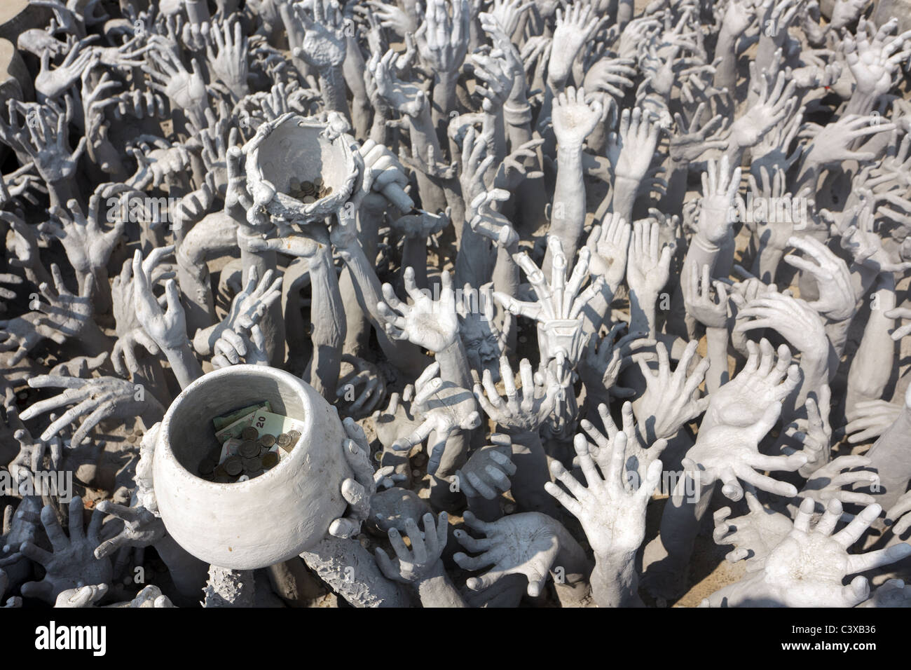 modern sculpture of raised human hands asking for charity including bowl with money,  wat rong khun temple, chiang - Stock Image