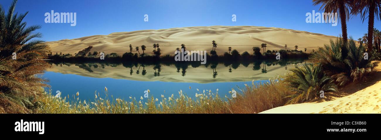 Libya, Ubari, Sahara Desert, Oasis with palm trees and lake. Um El Ma salt lake. - Stock Image