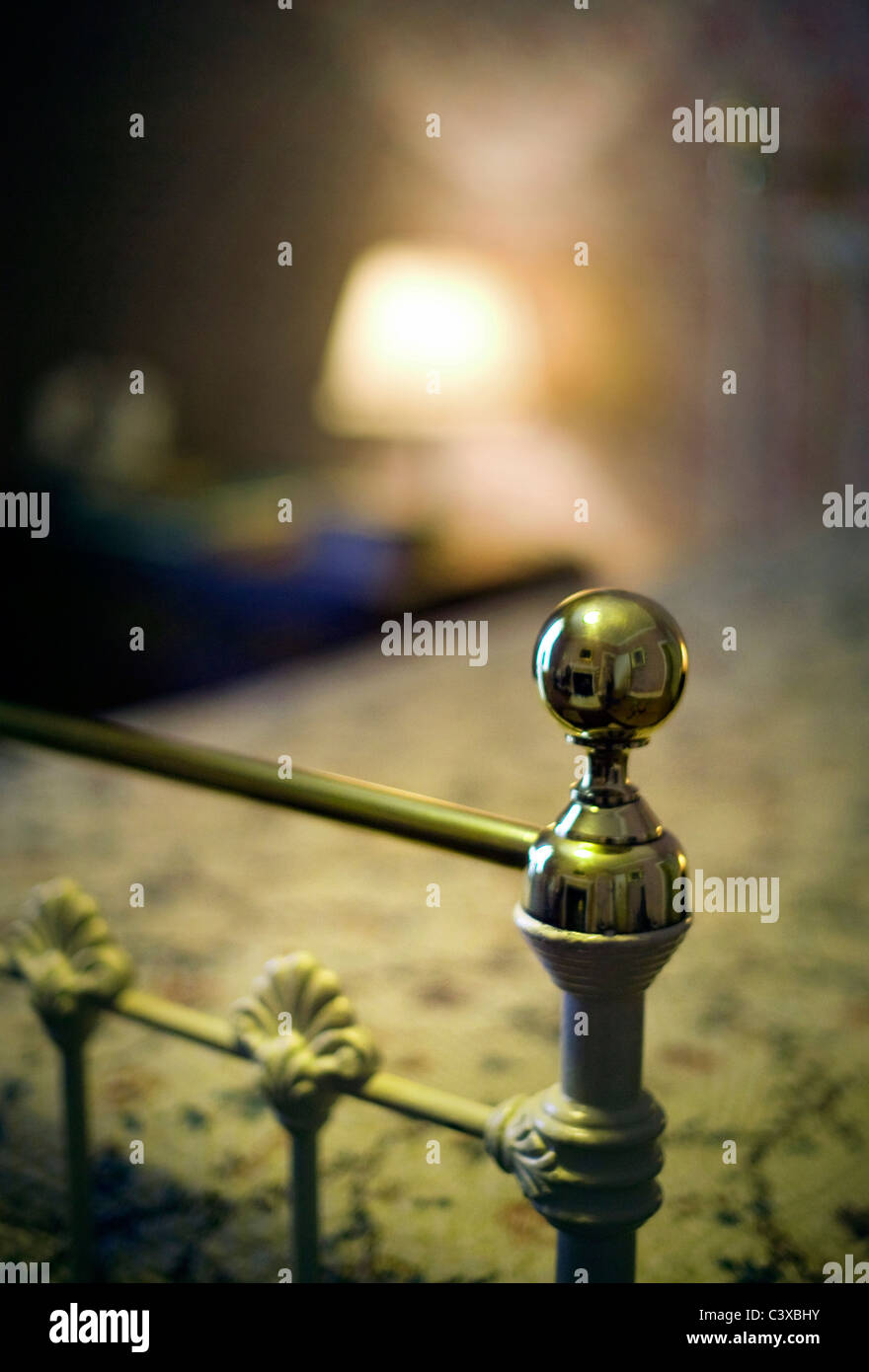 brass bedstead and table lamp - Stock Image
