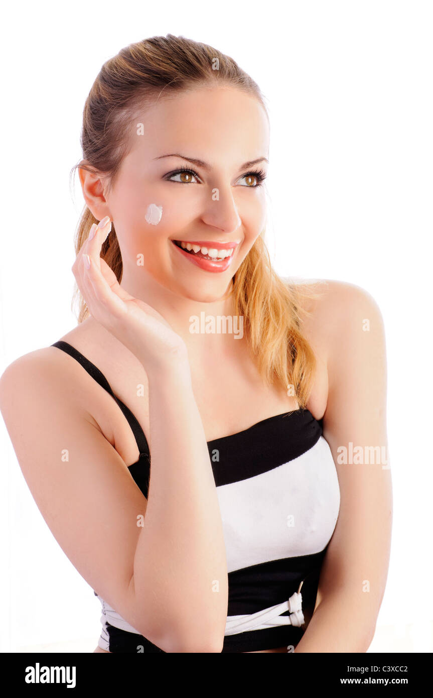 Beautiful girl with pony tail applying cream or moisturizer on her face and smiling, isolated - Stock Image