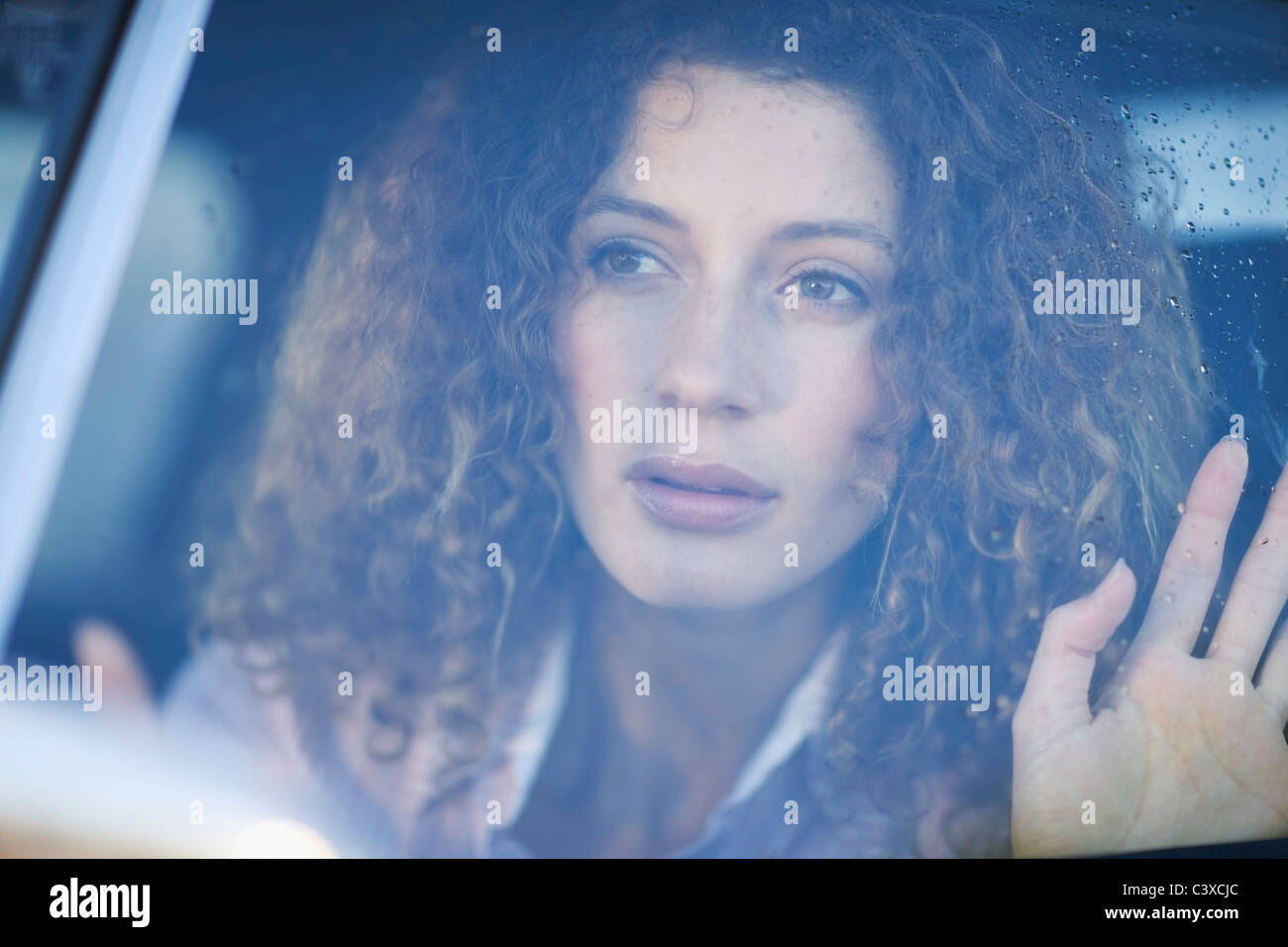 Woman looking out of a car window - Stock Image