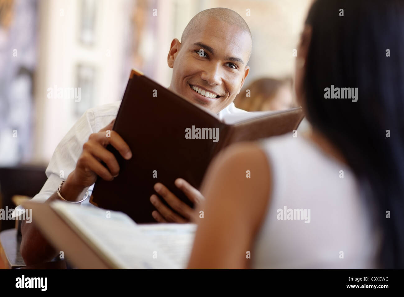 young adult hispanic couple dining out in restaurant and reading menu. Horizontal shape, waist up, focus on background - Stock Image