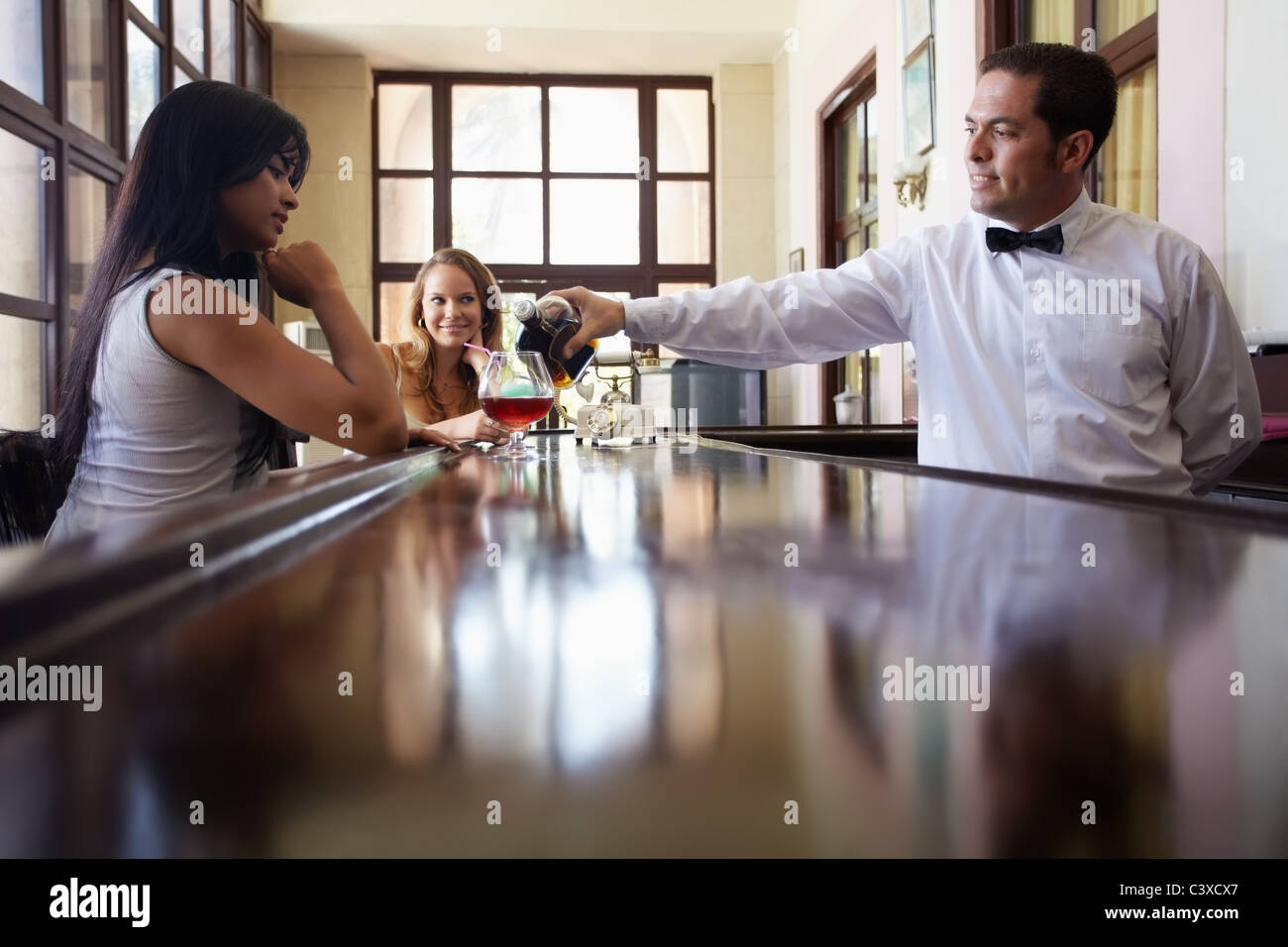 female friends sitting in pub and hispanic barman serving cocktail. Horizontal shape side view, copy space Stock Photo