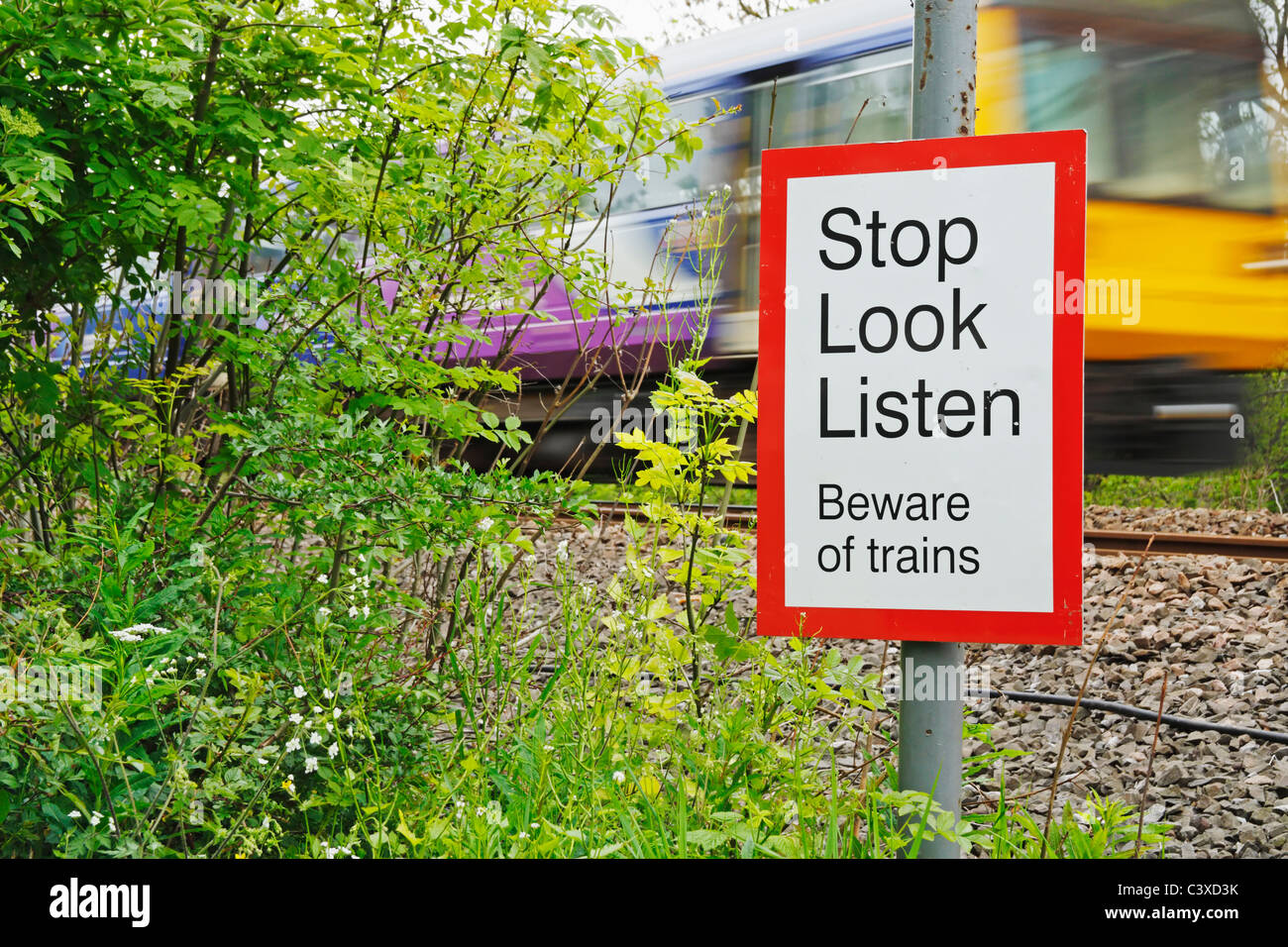 Northern Rail train passing pedestrian crossing point. England, United Kingdom - Stock Image
