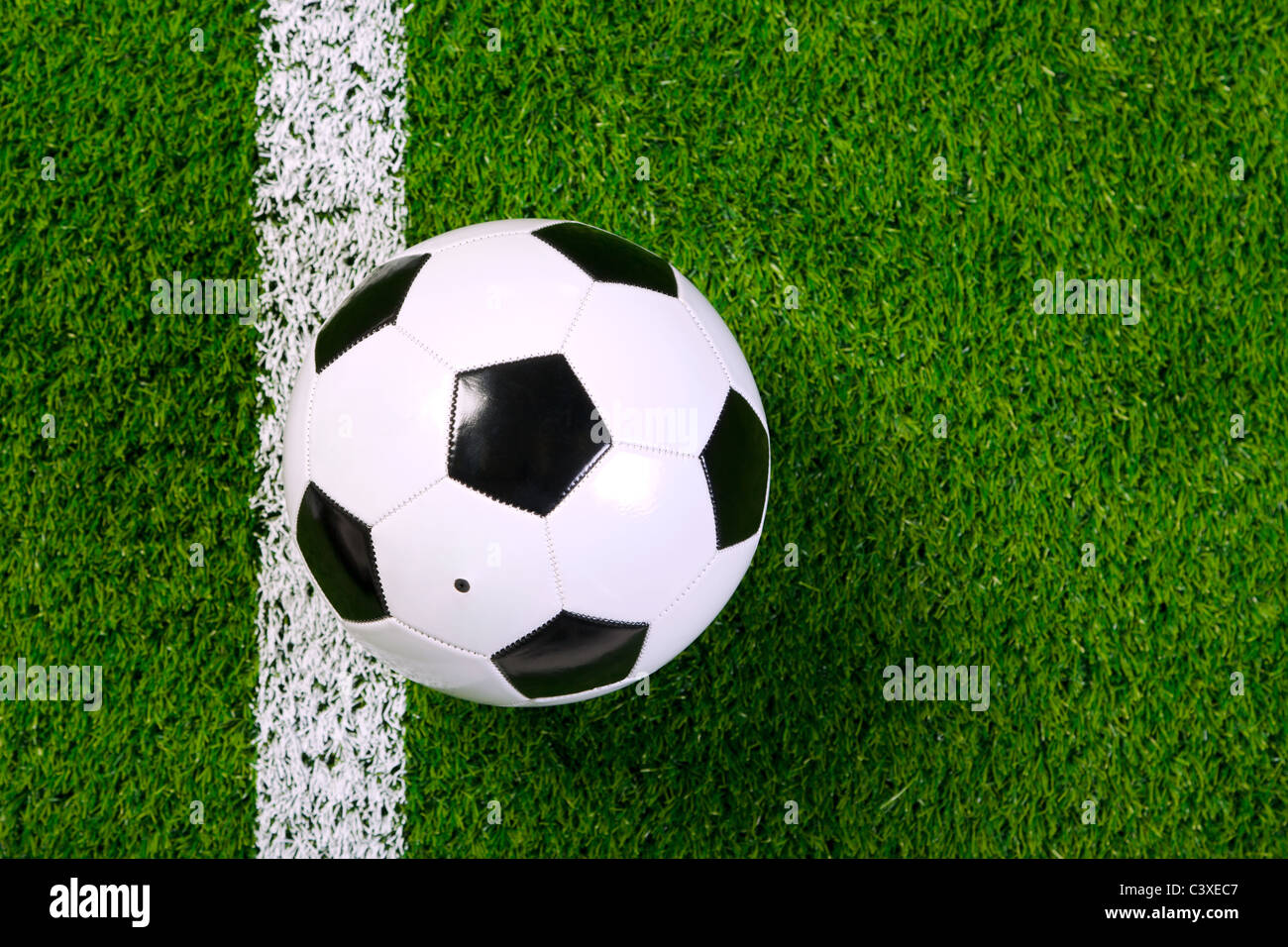 Photo of a leather football or soccer ball on a grass next to the white line, shot from above. - Stock Image