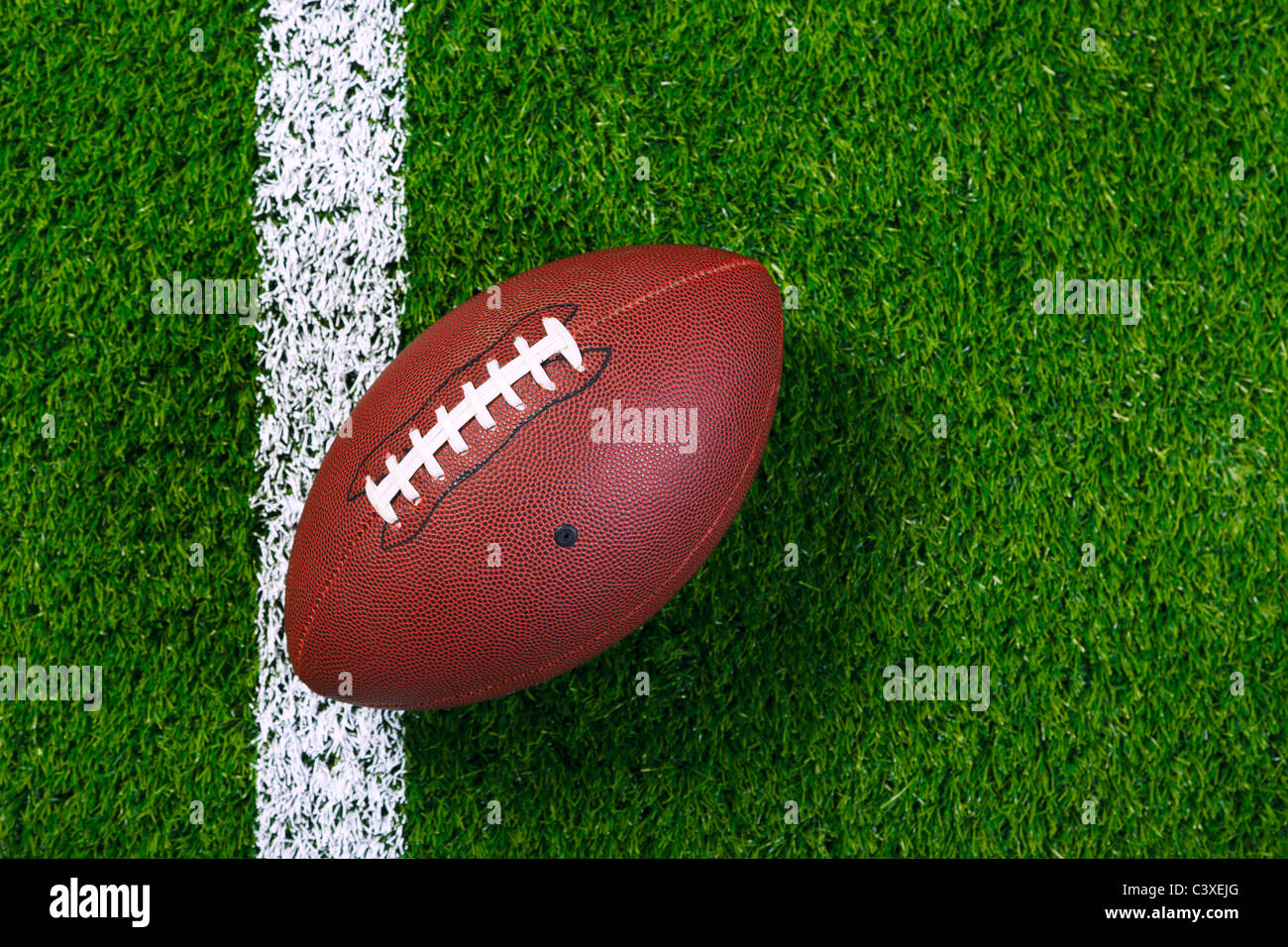 Photo of an American football on a grass next to the touchline, shot from above. - Stock Image