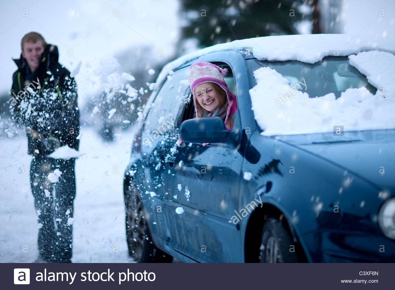 Playful man throwing snow at girlfriend sitting in car - Stock Image