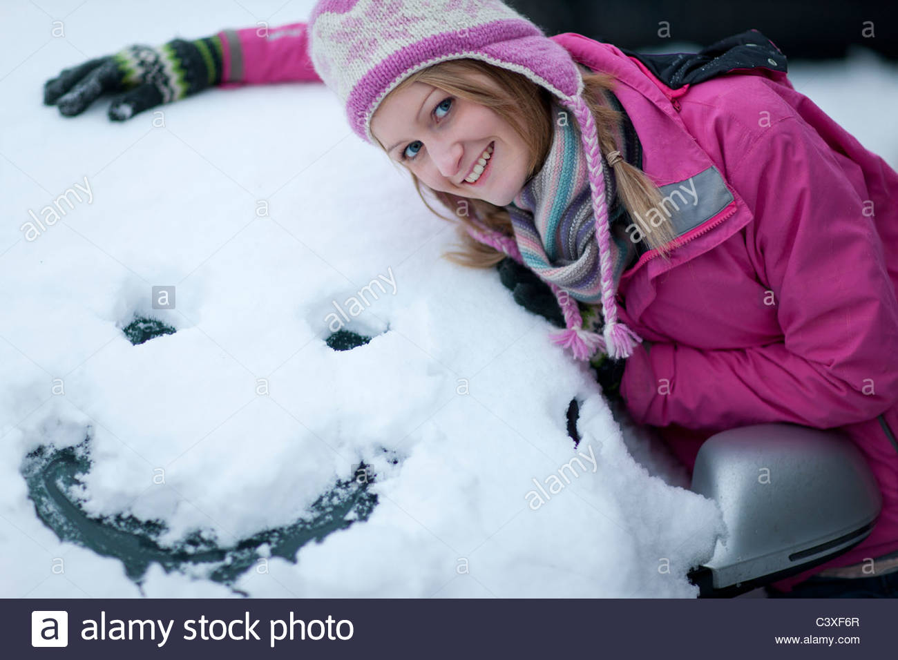 Woman making a face in snow on car windshield - Stock Image