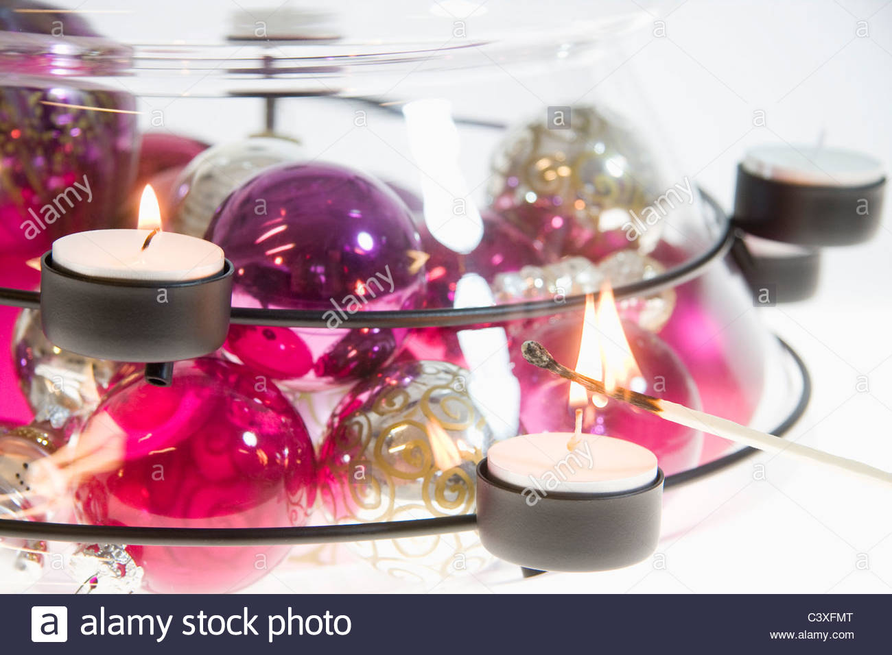 Lighting Candle in Candlestick Holder - Stock Image