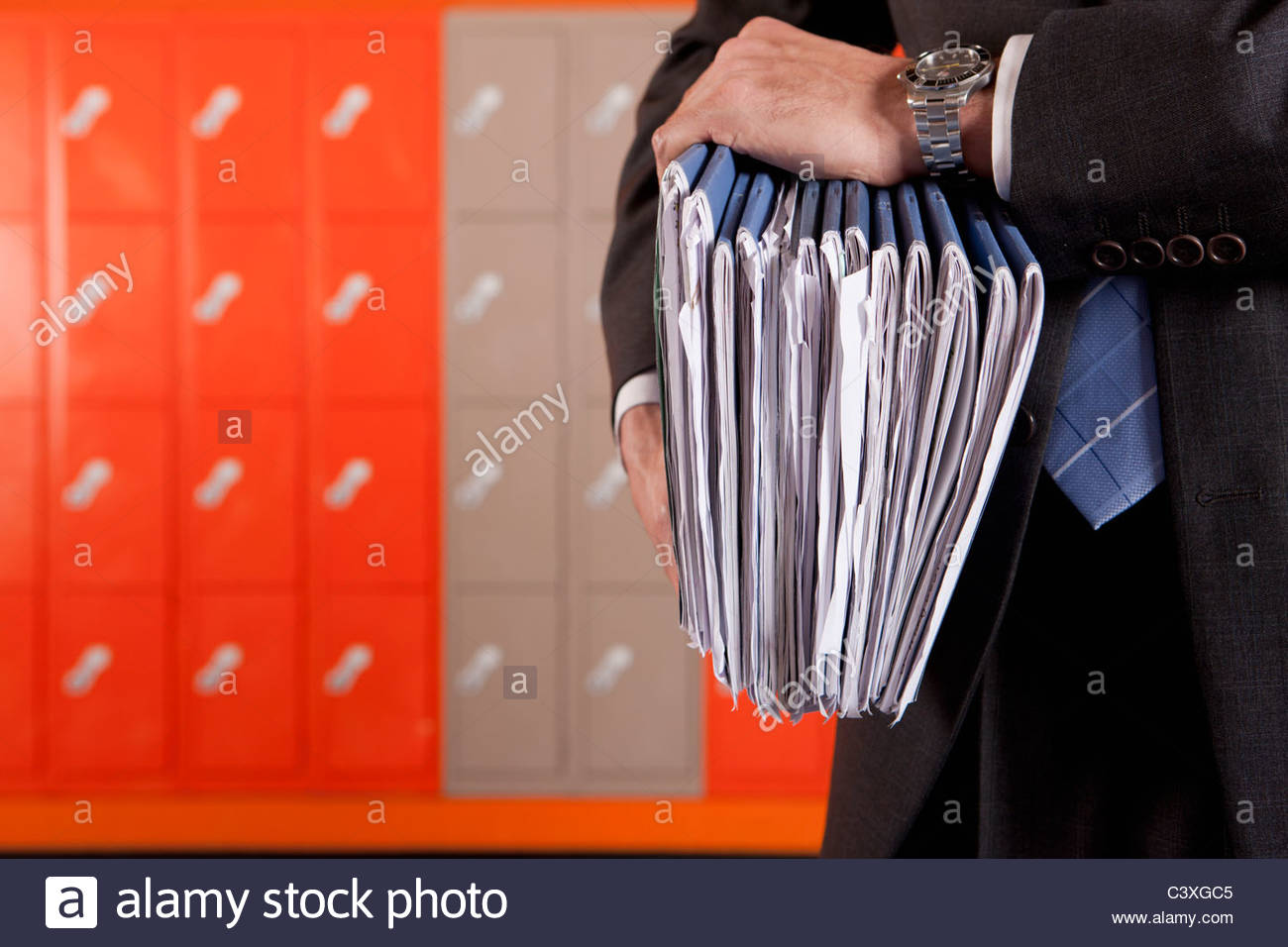 Close up of teacher holding paperwork near school lockers - Stock Image